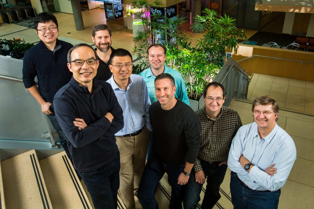 Microsoft researchers from the Speech & Dialog research group include, from back left, Wayne Xiong, Geoffrey Zweig, Xuedong Huang, Dong Yu, Frank Seide, Mike Seltzer, Jasha Droppo and Andreas Stolcke. (Photo by Dan DeLong)